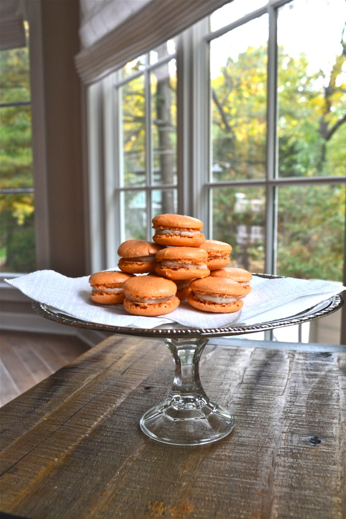A stack of pumpkin pie macarons with cream cheese filling on a cake stand.