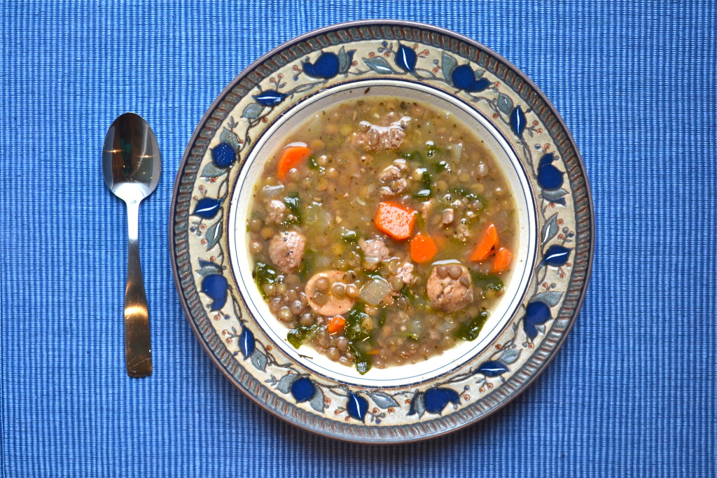 A bowl of chicken sausage lentil soup with carrots.