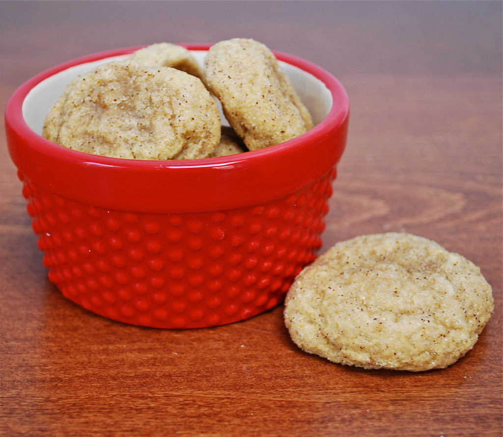 A pile of pumpkin snickerdoodle cookies in a red bowl with one cookie on the surface.