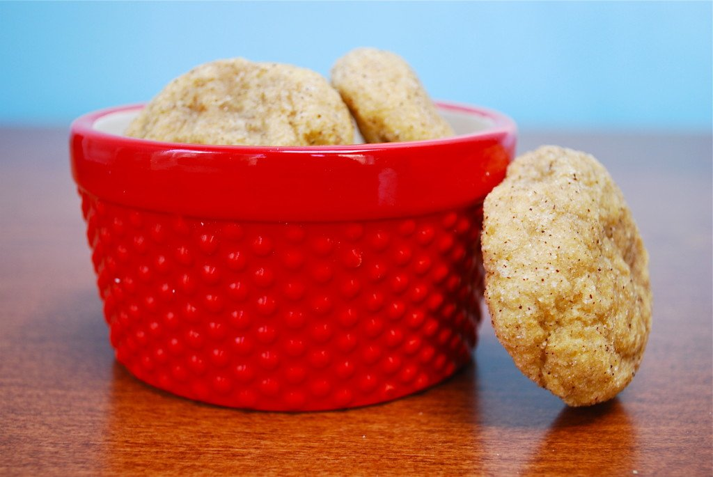 A pile of pumpkin snickerdoodle cookies in a red bowl with one cookie leaning against the bowl.
