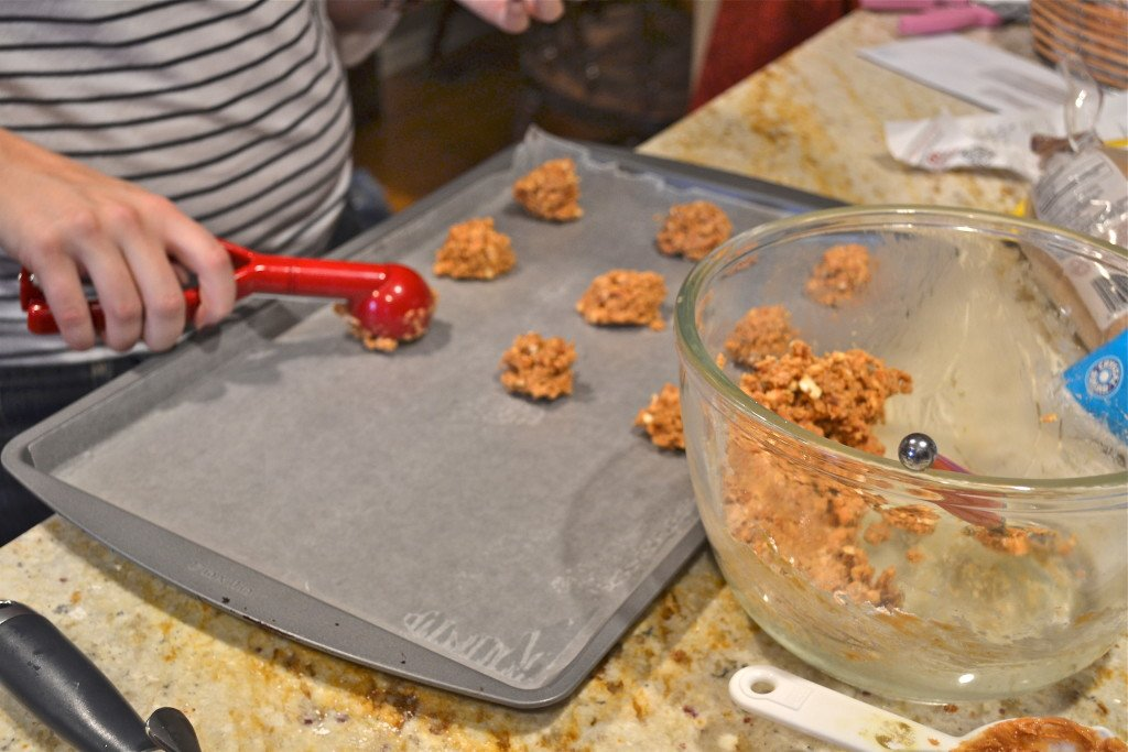 A cookie scoop portioning out peanut butter pretzel filling onto a baking sheet.