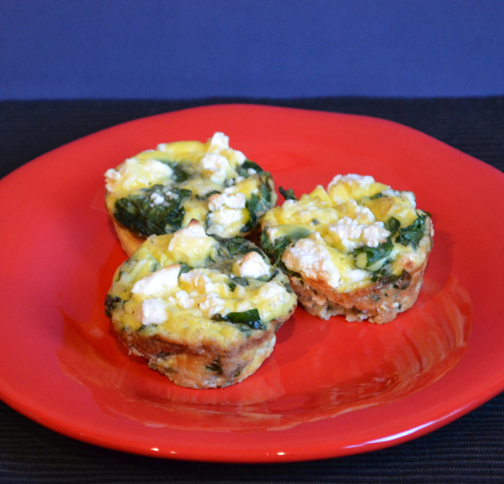Three spinach and feta mini omelets on a red plate.