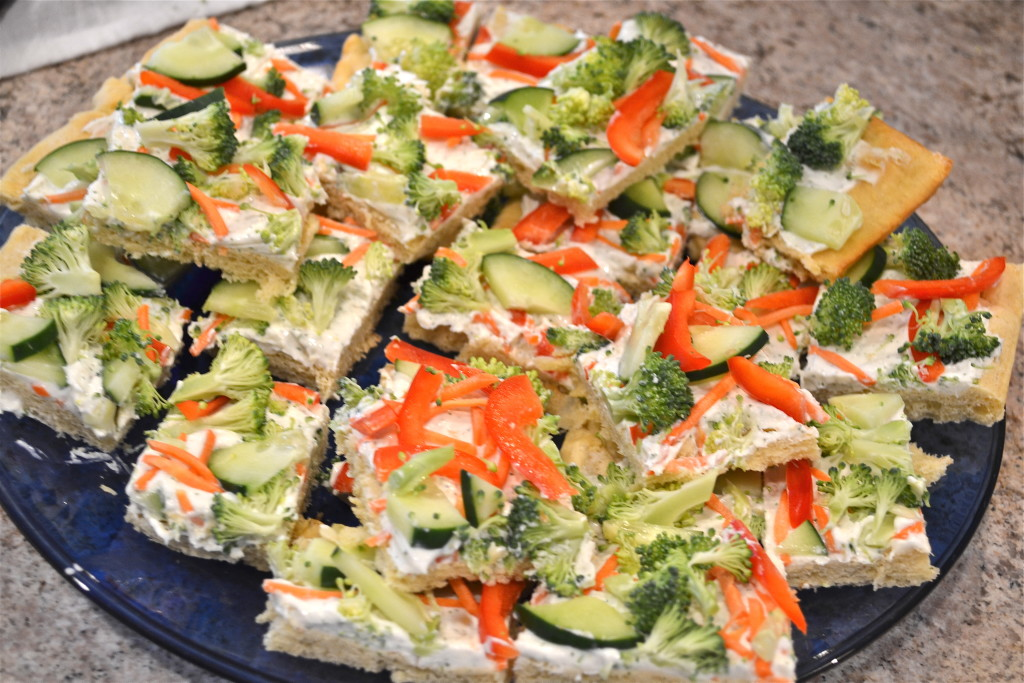 Slices of cold veggie pizza topped with cucumber, peppers, broccoli and carrots on a blue platter.