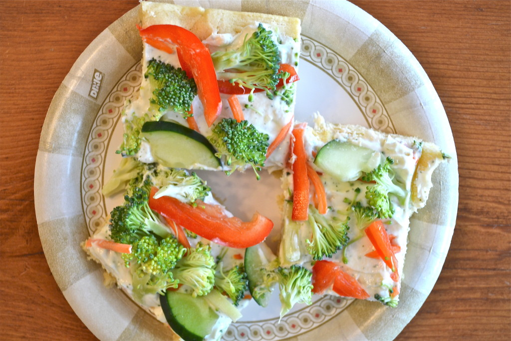Slices of cold veggie pizza topped with peppers, cucumber and broccoli on a paper plate.