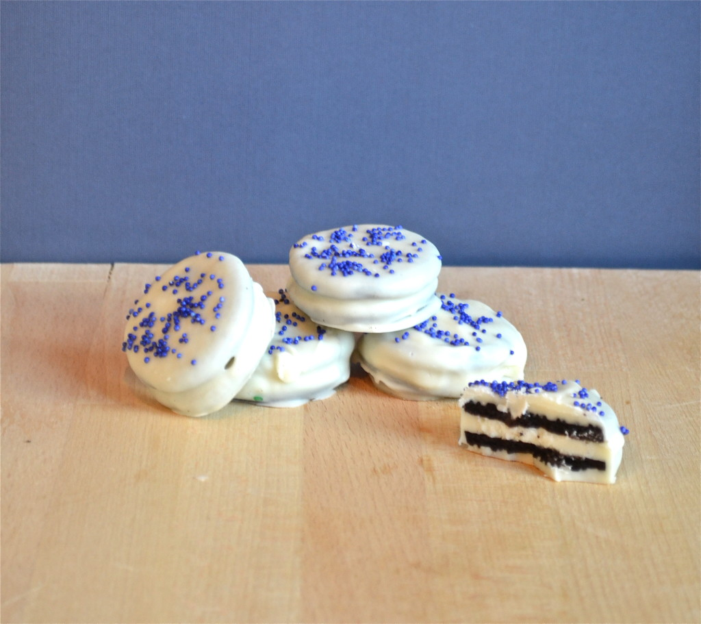 White chocolate covered oreos with blue sprinkles on a wood table.