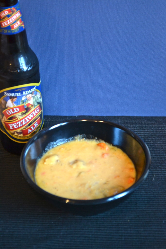 A bowl of beer cheese soup with a bottle of beer next to it.