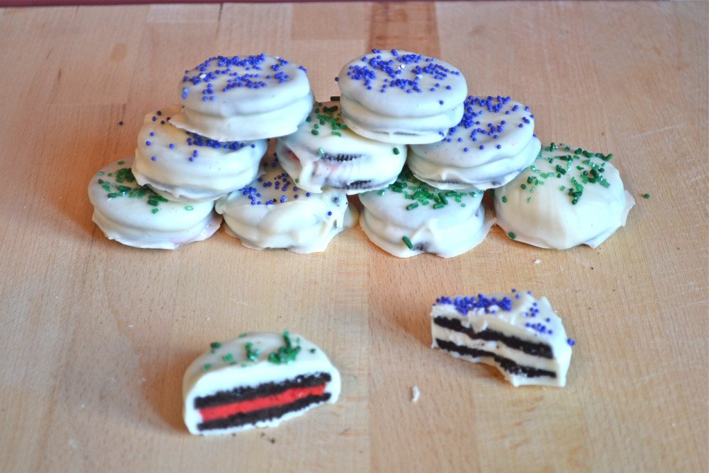 A stack of white chocolate covered oreos with blue and green sprinkles.