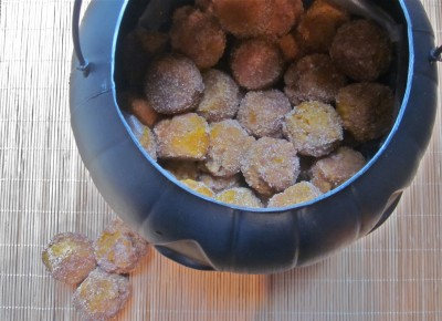 A pumpkin cauldron filled with pumpkin donut holes.