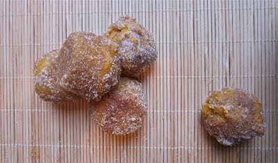 A stack of pumpkin donut holes rolled in sugar on a bamboo placemat.