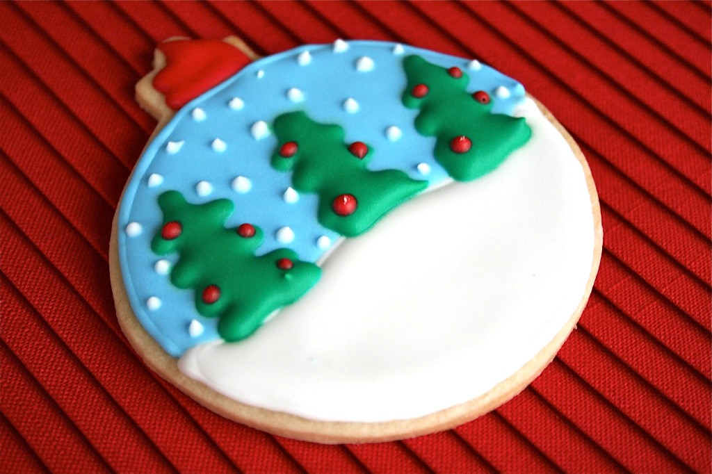 A snowglobe ornament sugar cookie on a red placemat.
