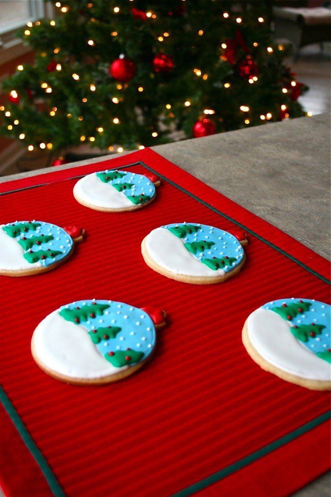 Five snowglobe ornament sugar cookies on a red placemat in front of a Christmas tree.