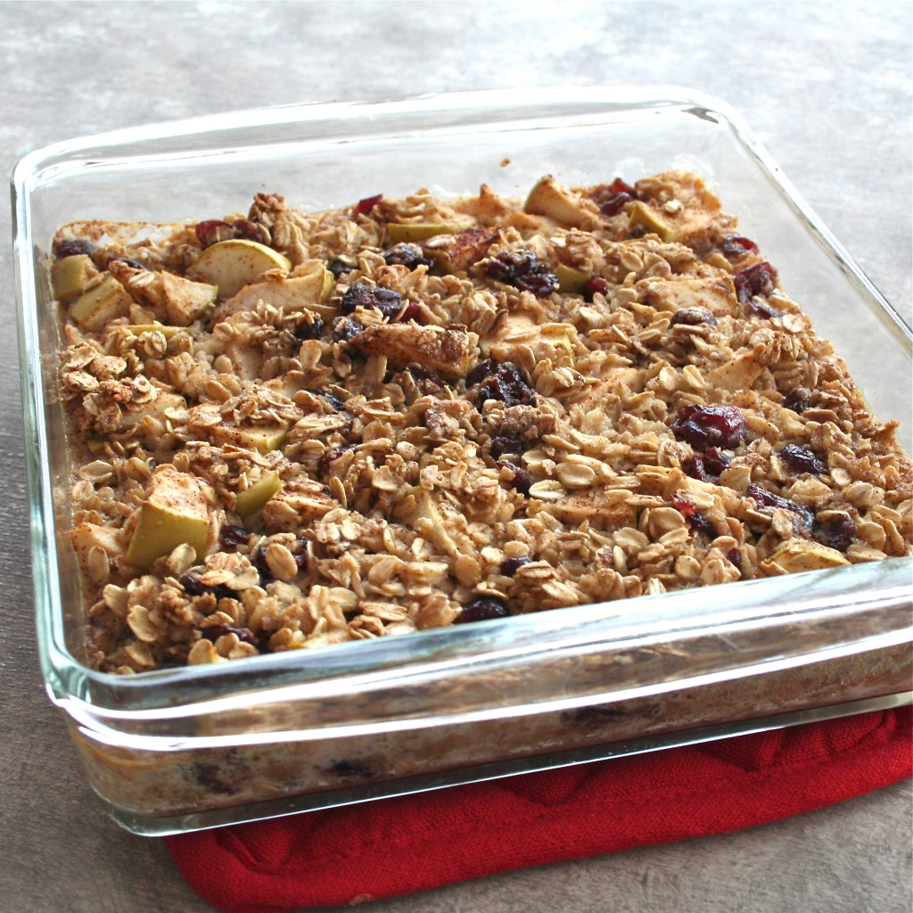 A casserole dish of apple baked oatmeal topped with dried cranberries.