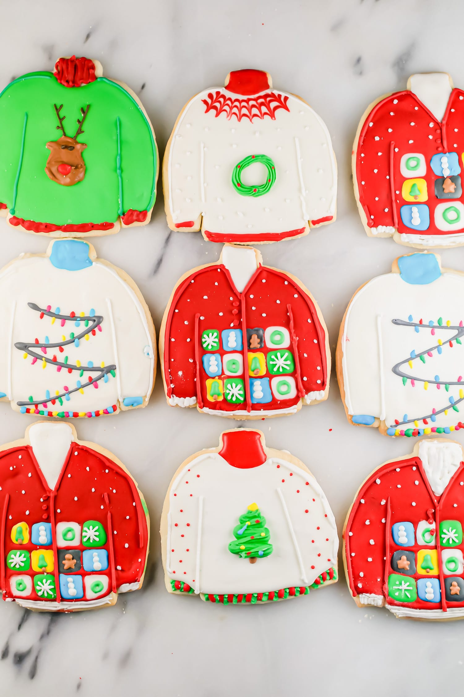 An overhead photo of rows of ugly sweater sugar cookies decorated with royal icing.
