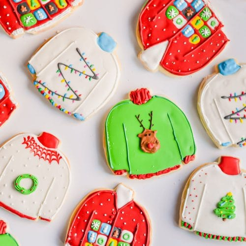An overhead photo of decorated gluten-free ugly sweater sugar cookies on a white surface.