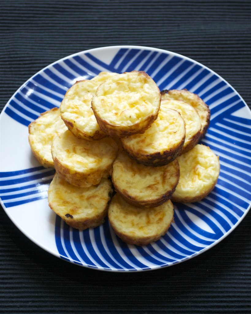 A pile of mini gluten-free quiches on a blue and white plate.