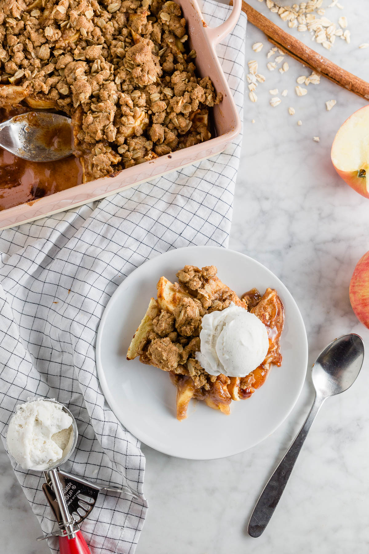 A plate with gluten-free apple crisp with a dairy-free and vegan option with a baking dish with sweet apple crisp.