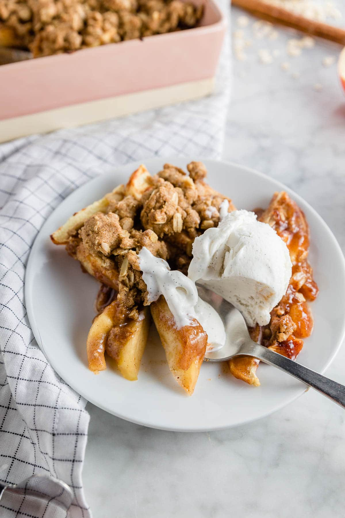 A white plate with gluten-free apple crisp with a scoop of melty vanilla ice cream with a spoon digging in.