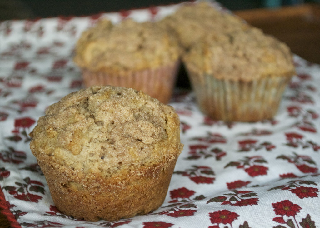 A gluten-free cinnamon streusel muffin on a floral napkin.