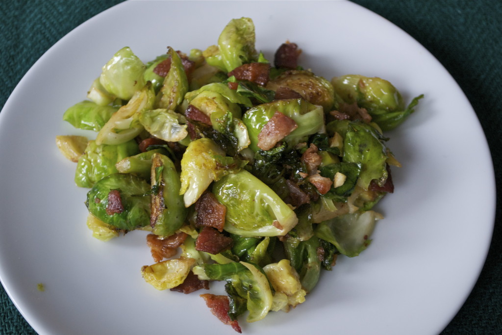 A plate of sautéd brussels sprouts topped with bacon.