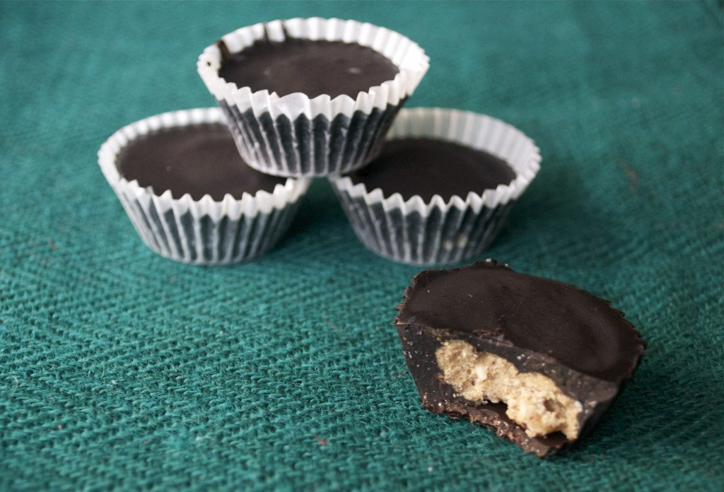 A pile of Chocolate Coconut Almond Butter Cups on a green placemat.