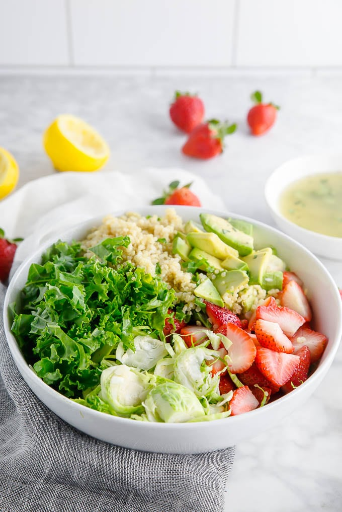 A bowl of kale, brussels sprouts, quinoa, avocado, and strawberries in a bowl ready to mix with lemon vinaigrette.