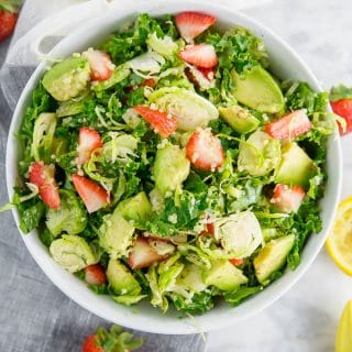 A bowl of brussels sprout kale salad with avocado, quinoa and strawberries.