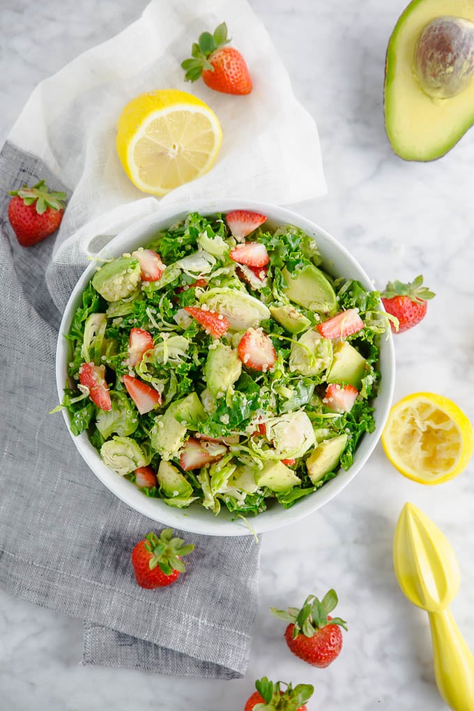A bowl of brussels sprouts kale salad with strawberries and lemon.