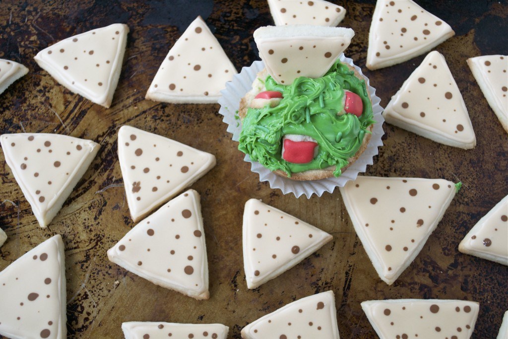 Sugar cookies decorated with royal icing to look like tortilla chips and guacamole on a baking sheet.