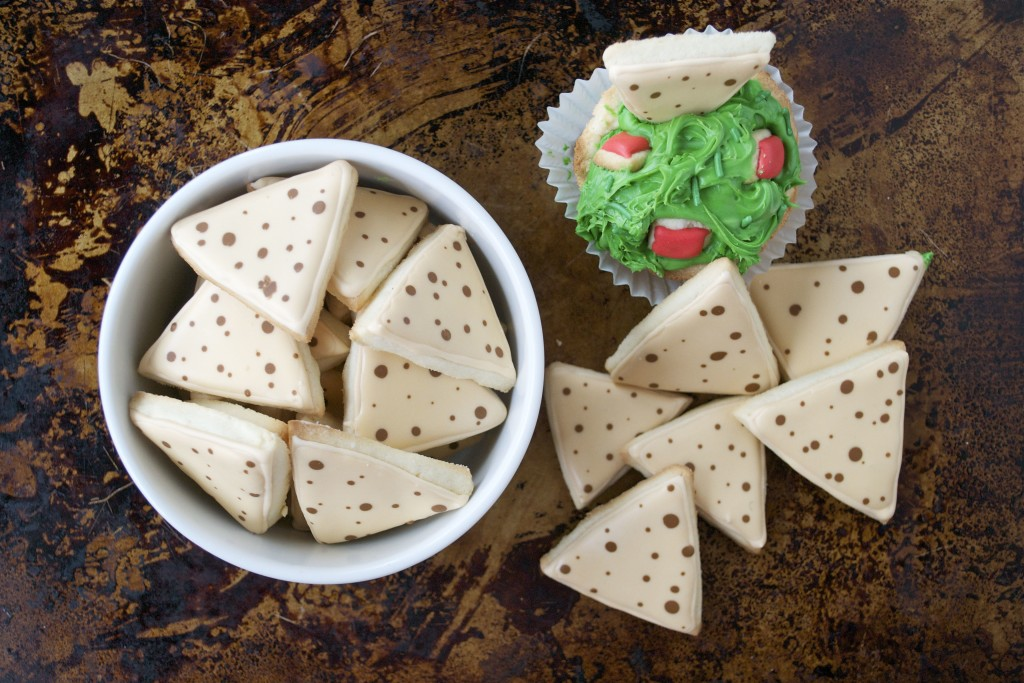 A ramekin of sugar cookies decorated like tortilla chips and a cup of buttercream to look like guacamole.