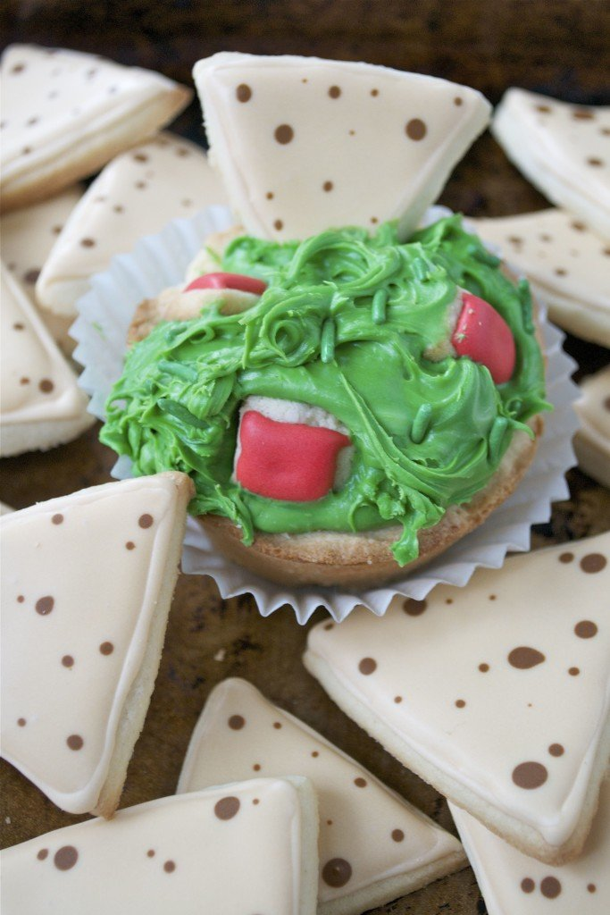Sugar cookies decorated with royal icing to look like tortilla chips and guacamole with tomatoes.