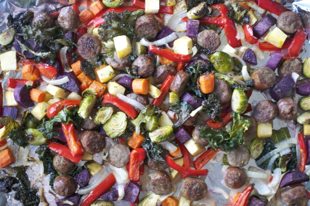 Roasted sausage, onion, purple sweet potato, red bell pepper, carrots, kale and brussels sprouts on a baking sheet lined with aluminum foil.