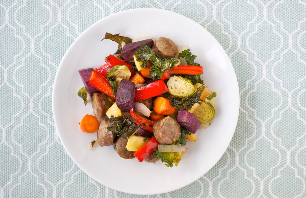 Roasted sausage, purple sweet potato, red bell peppers, brussels sprouts, carrots and kale on a white plate.