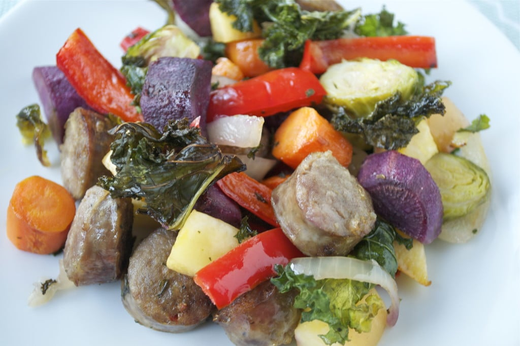 Roasted sausage, red bell peppers, brussels sprouts, carrots, kale, purple sweet potatoes, and onion on a white plate.