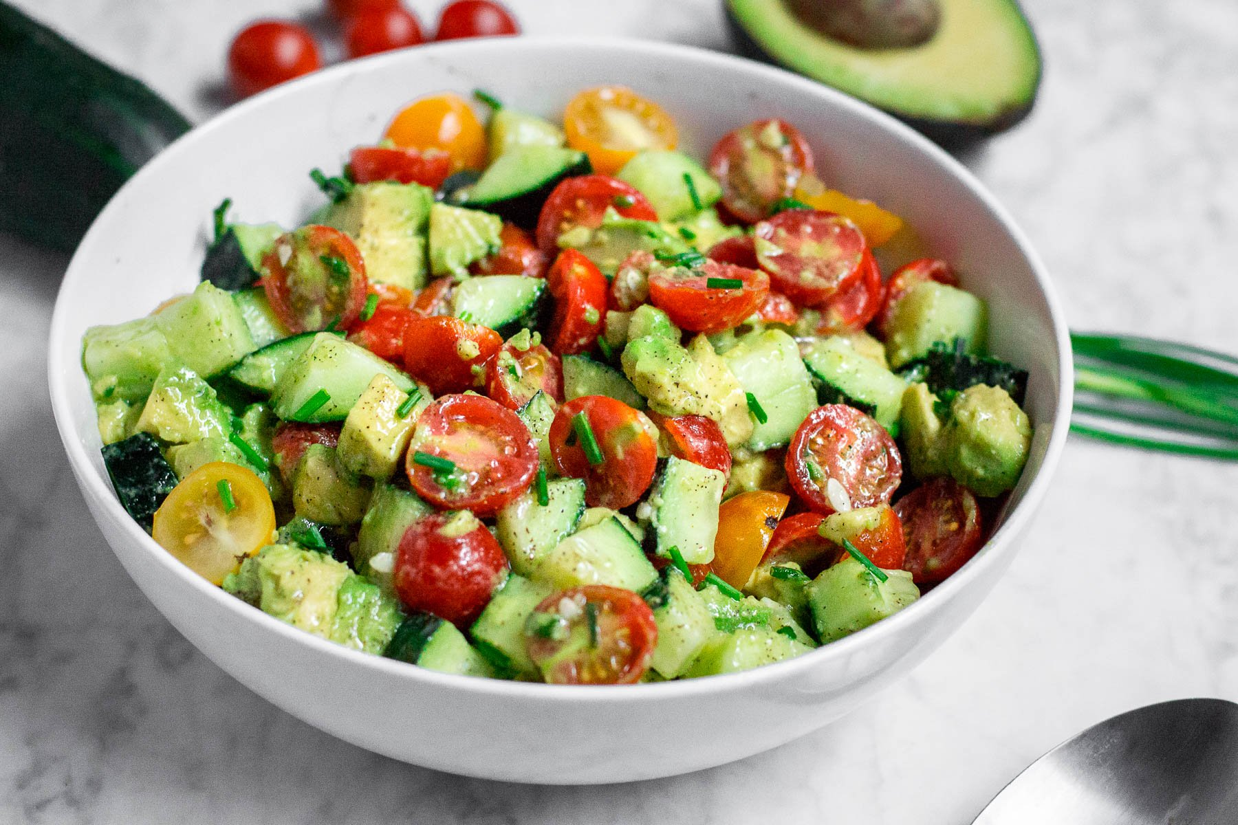 A white bowl filled with diced cucumbers, tomatoes, and avocado in a lemon dressing with chopped chives on top.