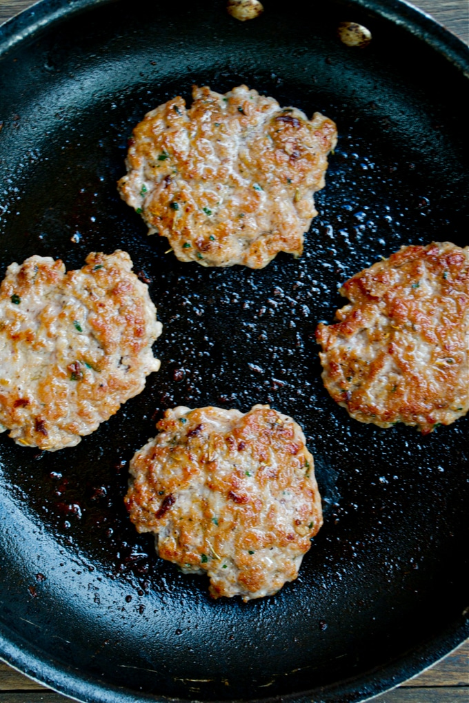 A non-stick skillet with four pork breakfast sausage patties.
