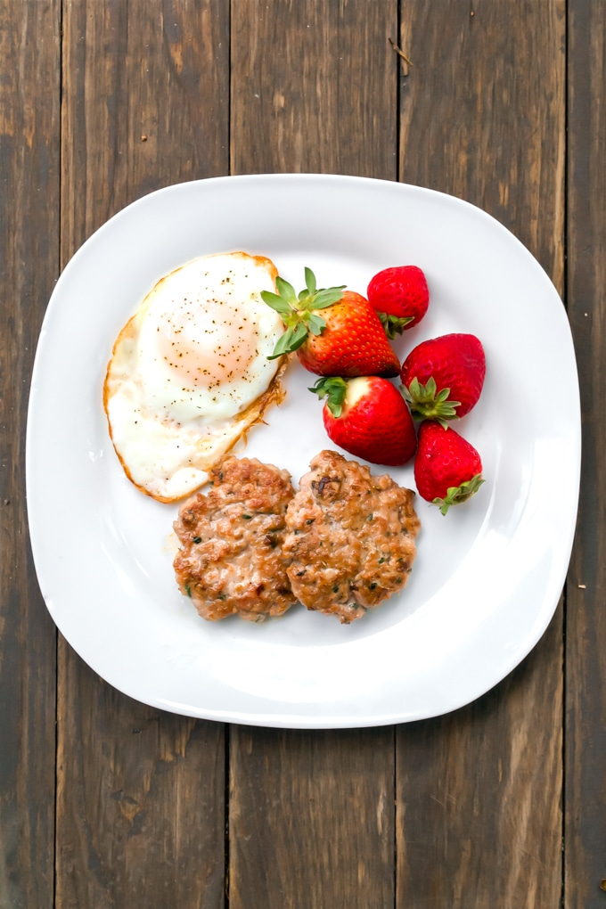A white plate with an over easy egg, pork breakfast sausage patties, and fresh strawberries.