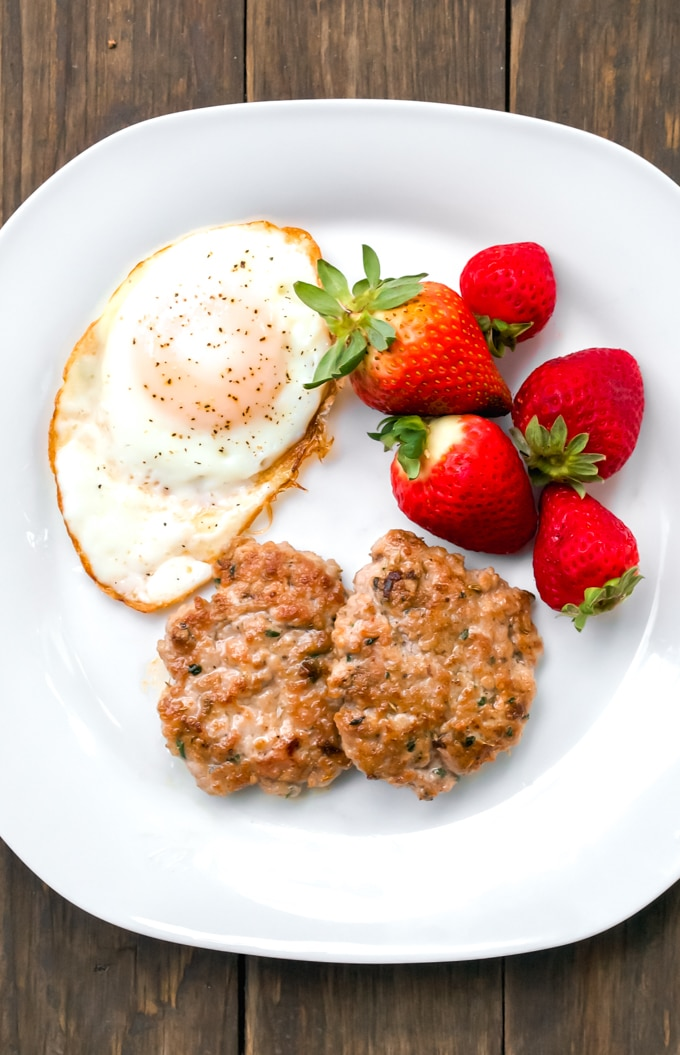 A white plate with two pork breakfast sausage patties, an over easy egg and fresh strawberries.