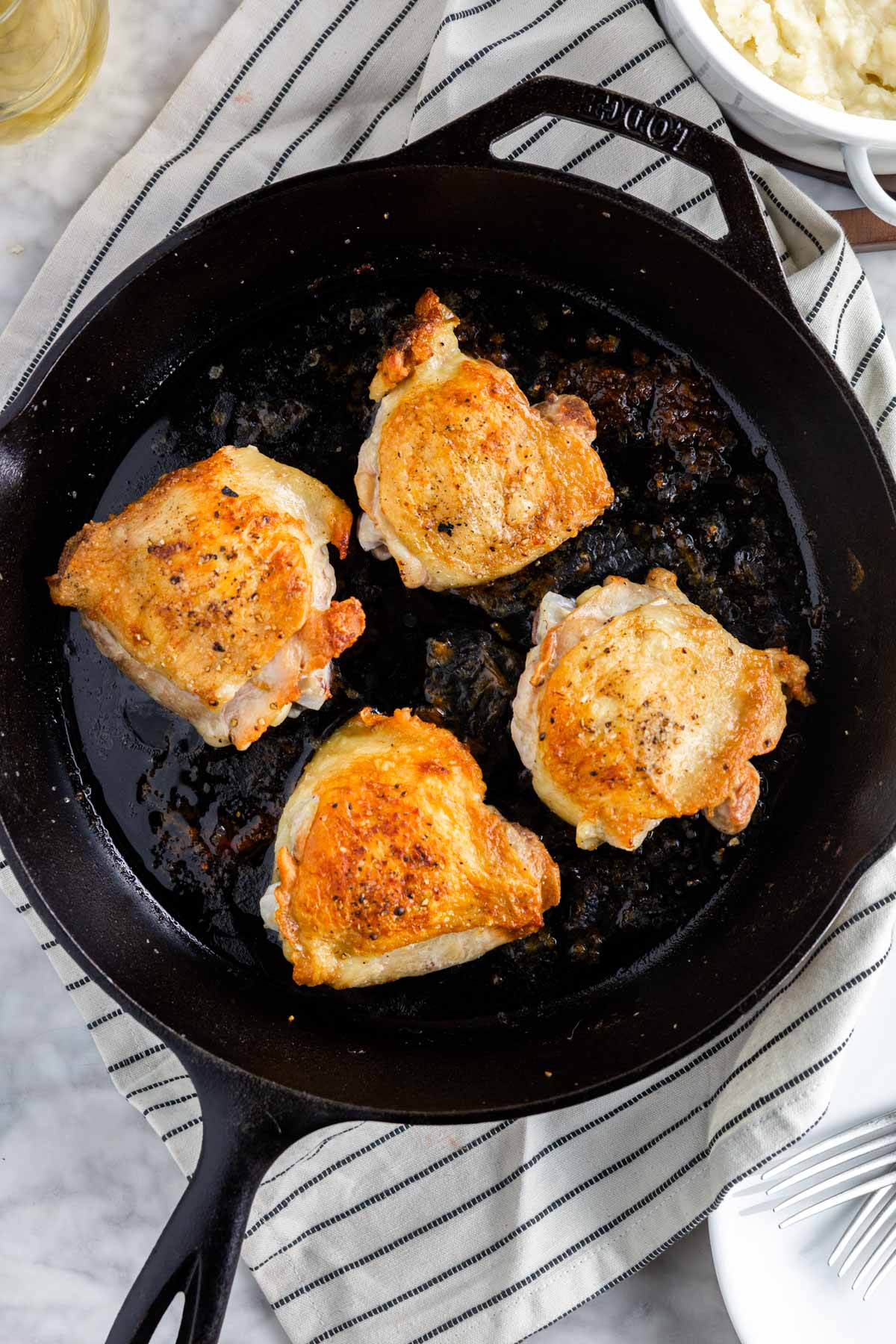 A cast iron skillet with four crispy chicken thighs with golden brown skin after baking in the oven.