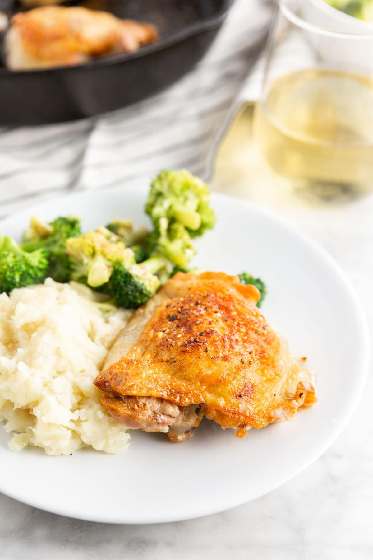 A dinner plate with roasted chicken thighs, mashed potatoes and steamed broccoli with a cast iron skillet and a glass of wine in the background.