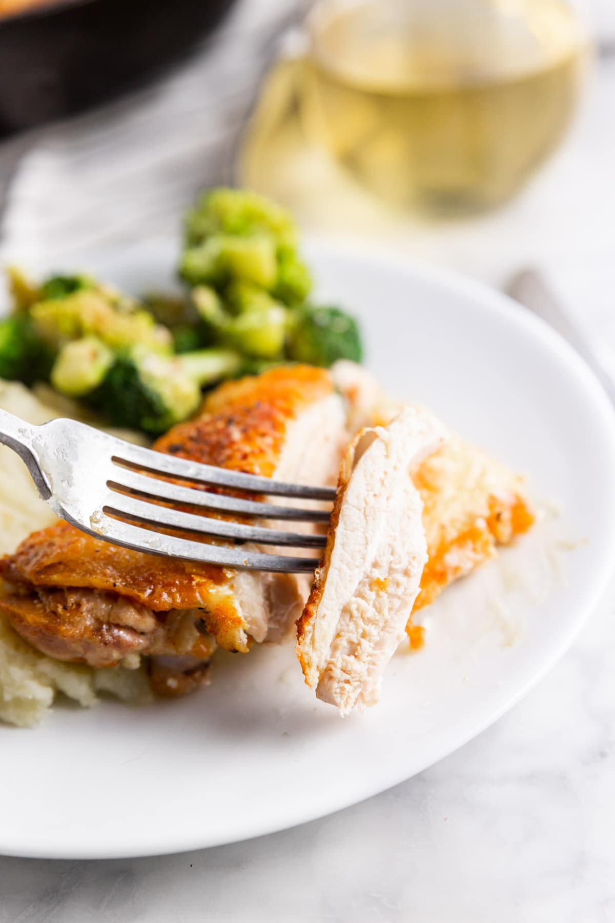 A plate with roasted chicken thighs with broccoli and mashed potatoes and a fork holding a slice of chicken.