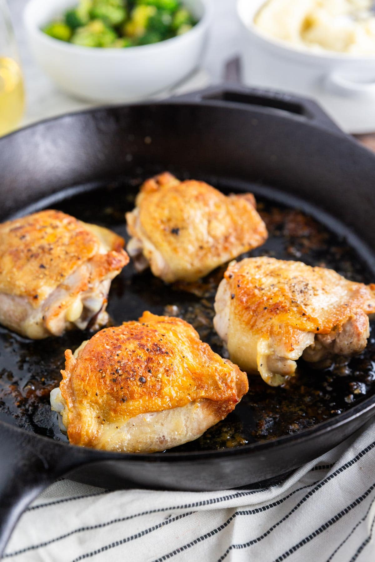 A photo of a large cast iron skillet with roasted chicken thighs in it topped with salt and pepper.