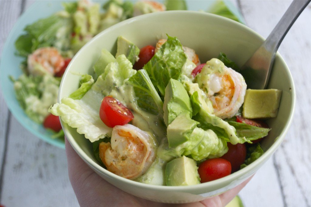 A bowl of salad with shrimp, avocado, cherry tomatoes, and creamy dressing next to a fork and half of an avocado.