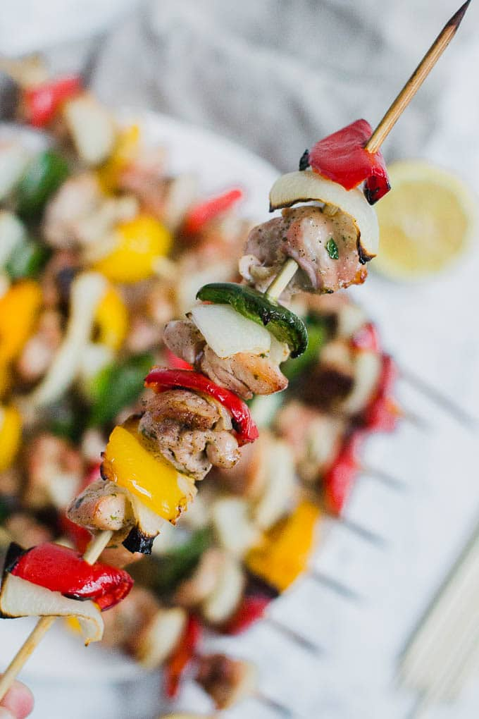 A wooden skewer alternating with chicken, bell peppers and onion.