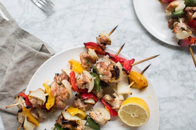 Aerial view of chicken kabob skewers on a platter with a lemon wedge and a small plate of kabobs for serving.