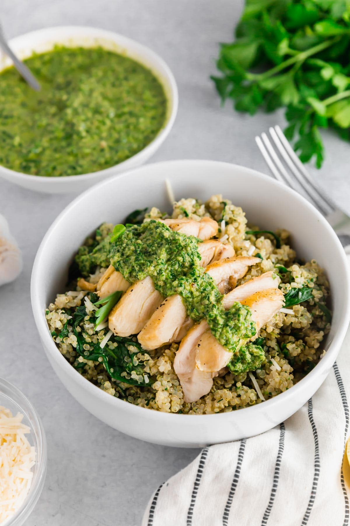A photo of of a bowl with quinoa and chicken topped with homemade vegan parsley walnut pesto.