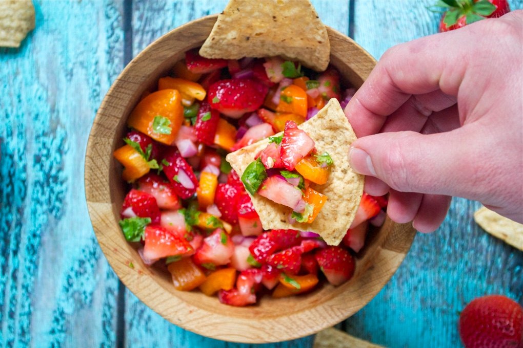 A hand holding a tortilla chip with strawberry salsa on it over a bowl of salsa.