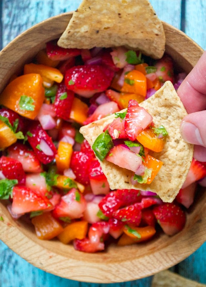 A hand holding a tortilla chip with strawberry jalapeño salsa over a  wood bowl.
