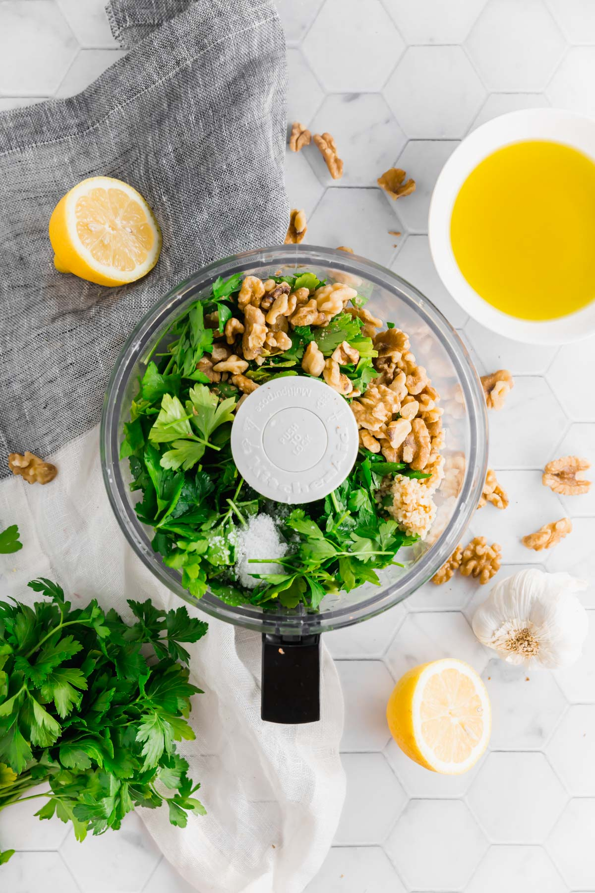 An overhead photo of a food processor filled with fresh parsley, garlic, walnuts, and salt to make vegan walnut parsley pesto.