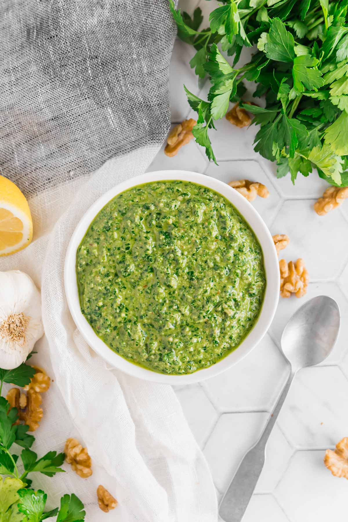 An overhead photo of a small bowl filled with vegan parsley walnut pesto with a spoon, fresh parsley, walnuts, garlic and lemon on a table.