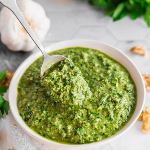A photo of a bowl of vegan parsley walnut pesto with a spoon in it surrounded by a bulb of garlic, half a lemon, a bunch of parsley and walnuts on a table.